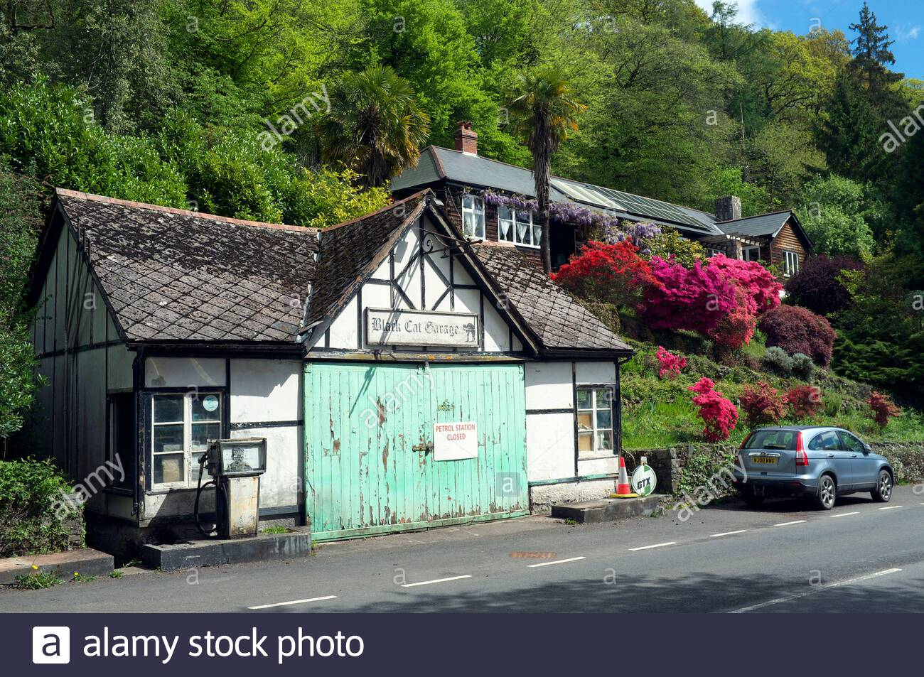 The closed down Black Cat Garage, and adjacent occupied residential property, on the A396 road in mid-Devon, south west England, UK. Stock Photo