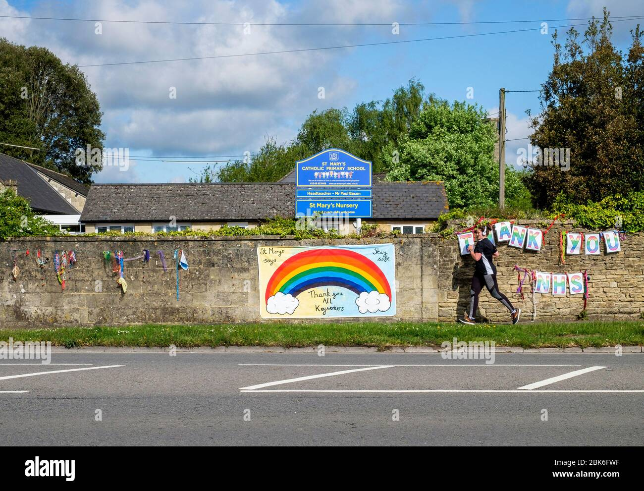 Chippenham, Wiltshire UK, 2nd May, 2020. A person out running is pictured as they run past 'thank you NHS' and 'thank you all key workers' signs that have been hung on a primary school wall opposite Chippenham Hospital. Credit: Lynchpics/Alamy Live News Stock Photo
