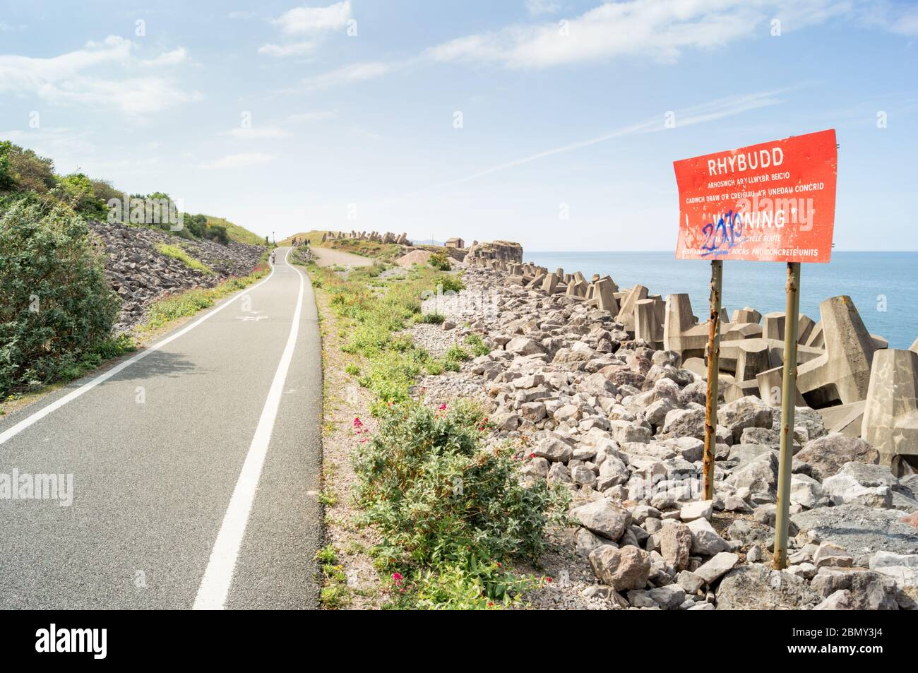 Cycle route path on the North Wales Expressway. Sign warns to keep away from the rocks and concrete units (dolos / dolosse) Stock Photo