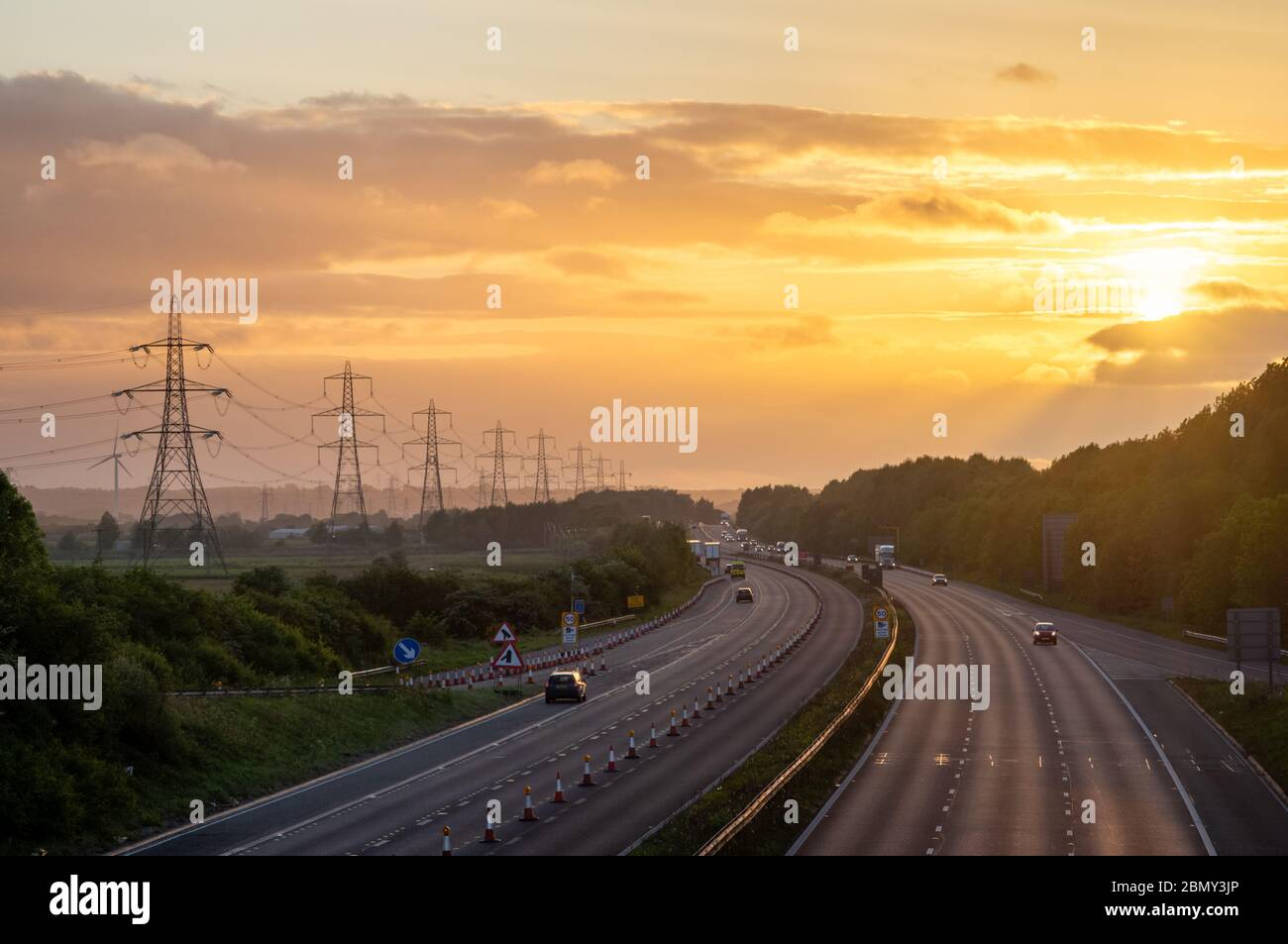 M56 motorway with pylons at sunrise Frodsham Cheshire UK concept early start commute power industry workers back to work daily grind Stock Photo