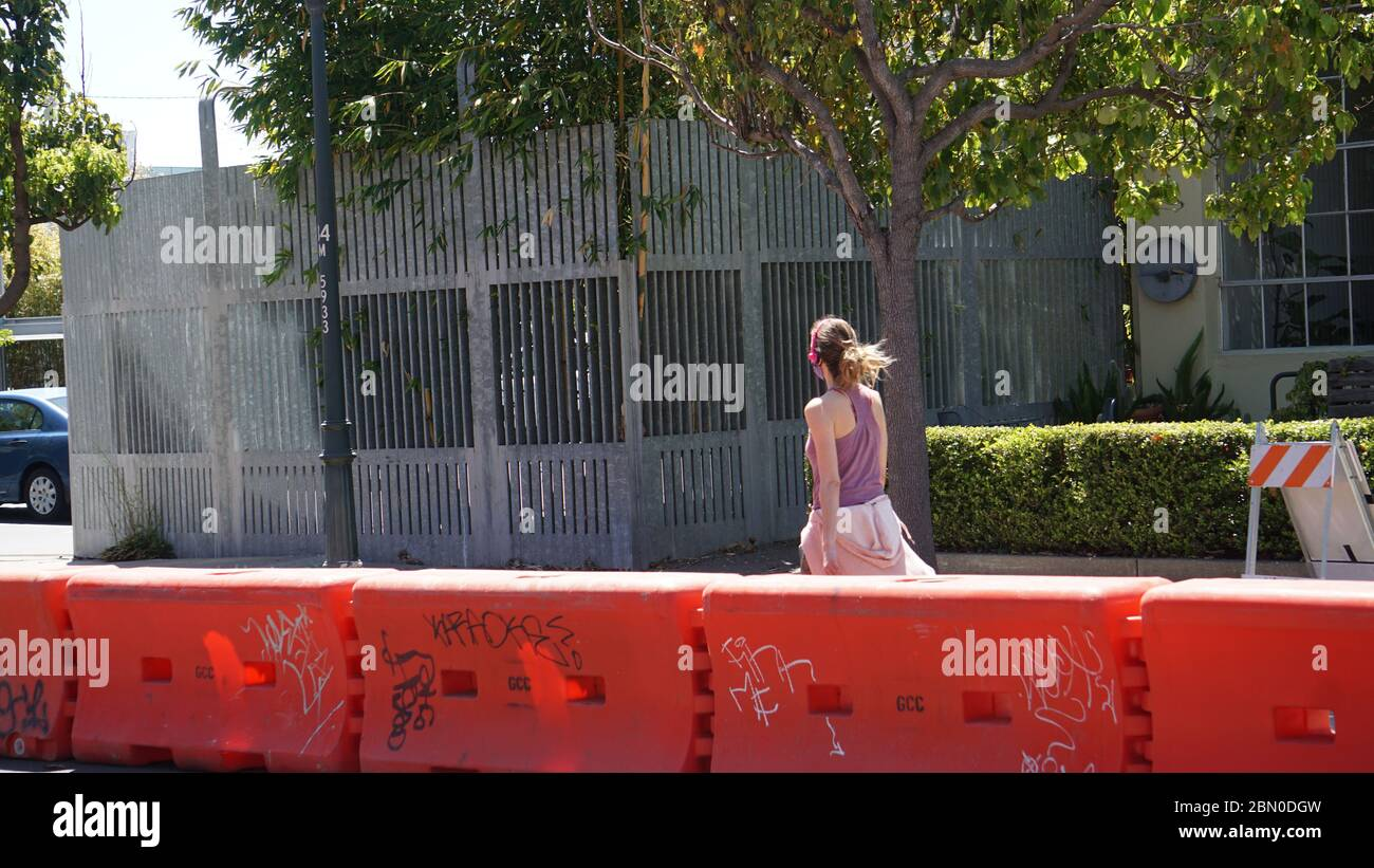 Woman walking with headphones on closed street reserved for pedestrians only to support social distancing due to COVID19. Emeryville, CA, USA. Stock Photo