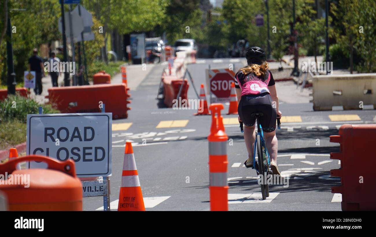 Bicyclist on street closed for COVID19, for pedestrians and bicycles only, to allow exercise and support social distancing. Emeryville, CA, USA. Stock Photo