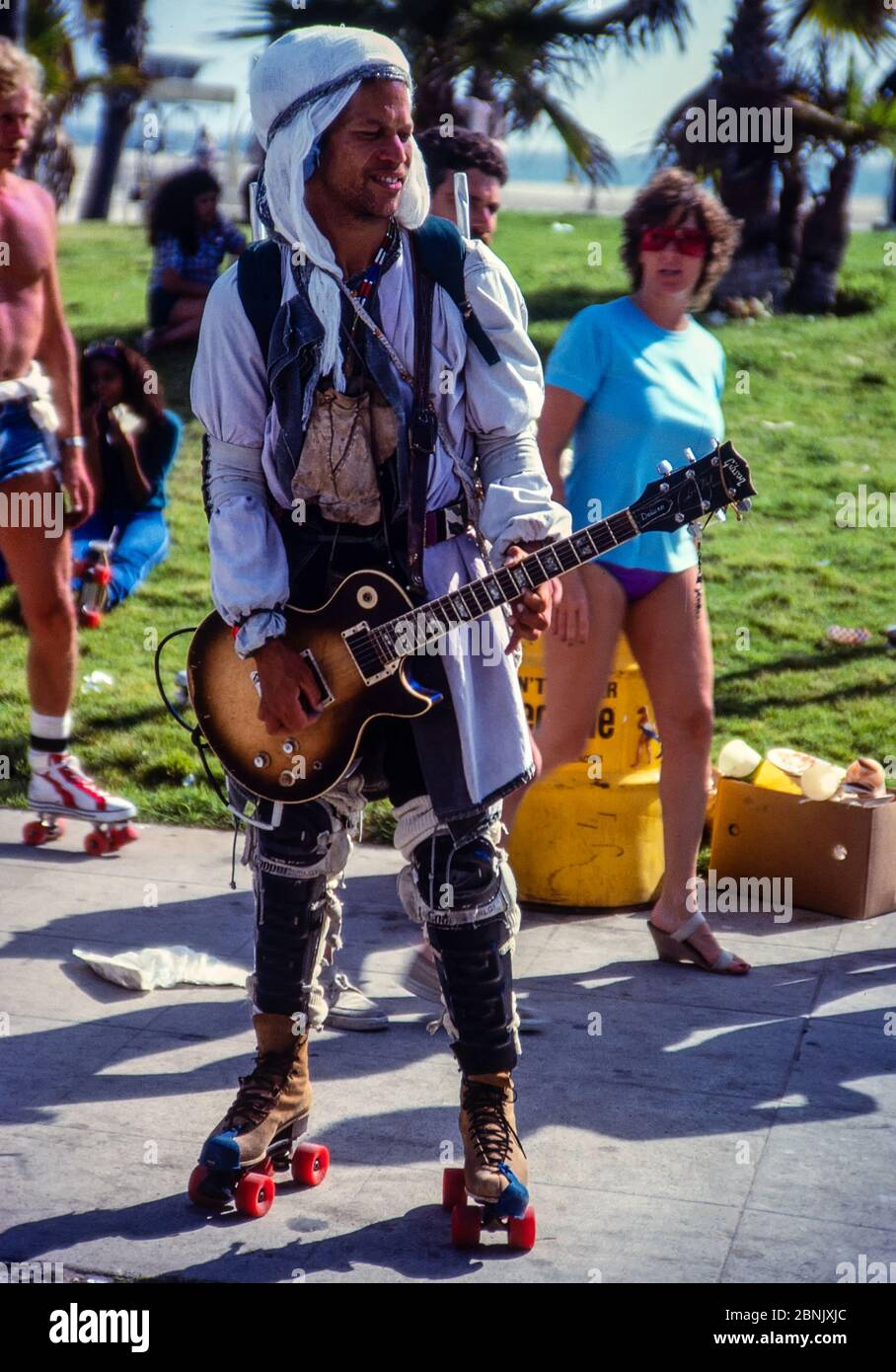 Venice, California, USA - May, 1981: Electric guitarist on rollerskates, playing on the beach boardwalk in Venice, California.  Scanned 35mm film. Stock Photo