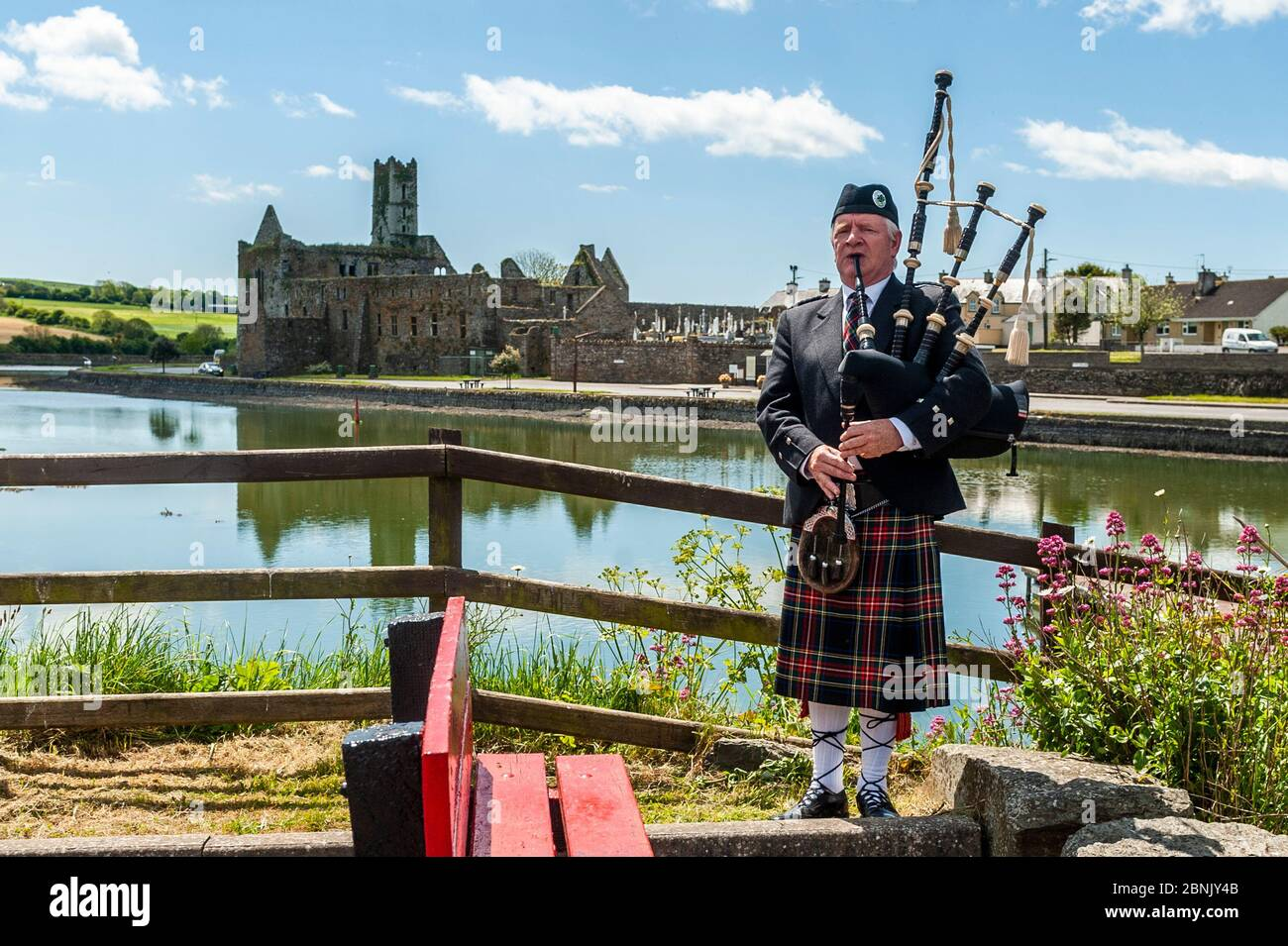 timoleague-west-cork-ireland-15th-may-2020-local-man-michael-heaney-from-timoleague-plays-the-bagpipes-with-timoleague-abbey-in-the-background-mr-heaney-was-filmed-playing-the-pipes-as-part-of-arigideen-rangers-gaa-clubs-fundraising-initiative-the-gaa-club-is-raising-money-for-clonakilty-community-hospital-pieta-house-and-timoleague-parish-church-credit-ag-newsalamy-live-news-2BNJY4B.jpg