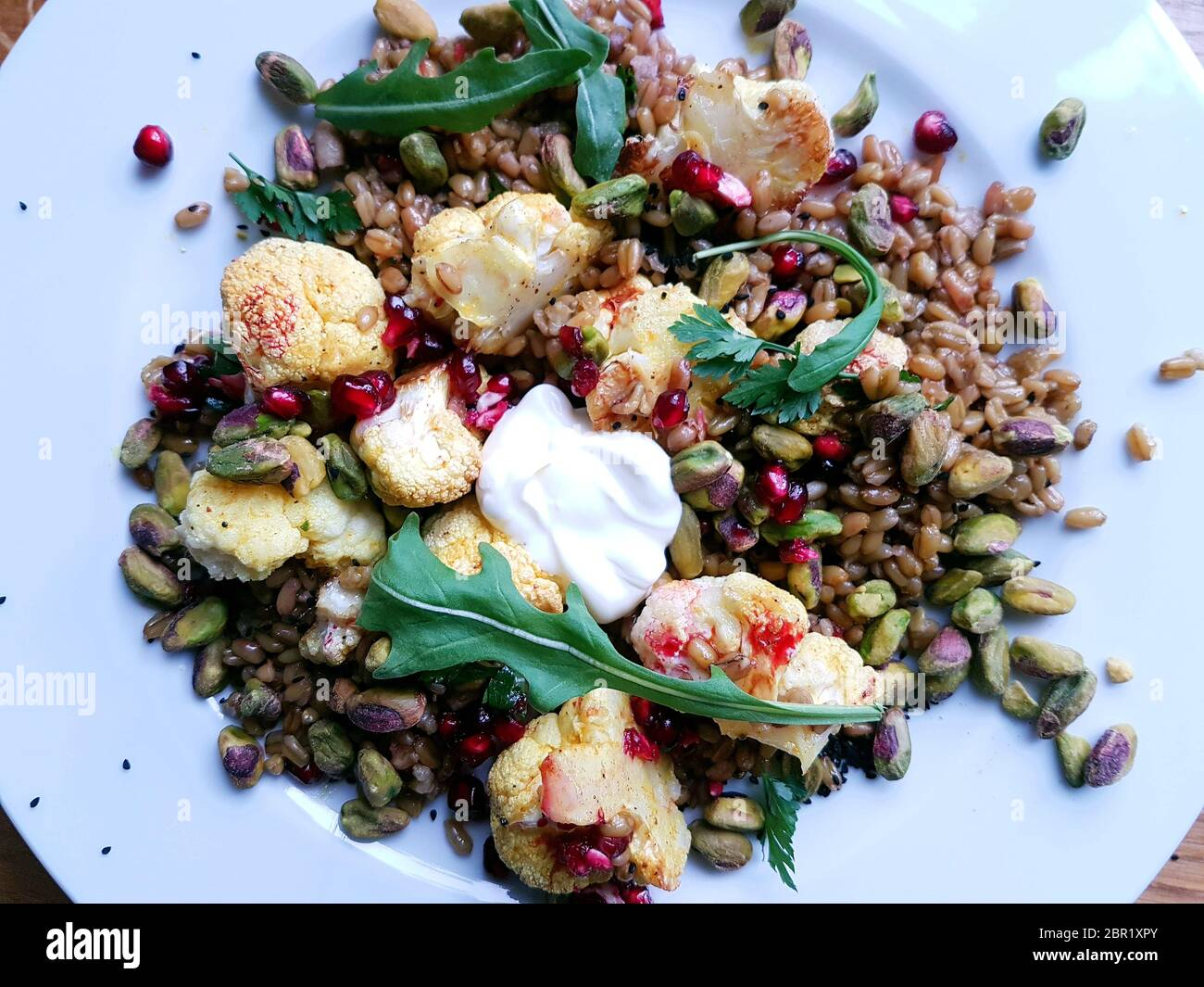 Freekeh, cauliflower and pomegranate salad with flat leaf parsley Stock Photo