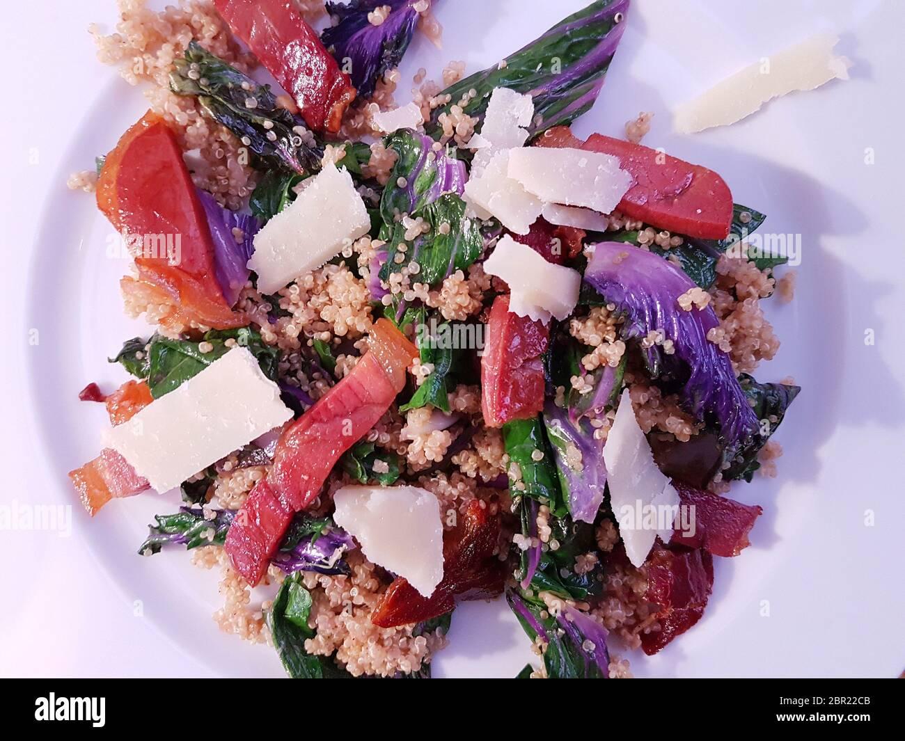 Recipe of Kale, shaved pecorino and Serrano ham with Quinoa on a white plate Stock Photo