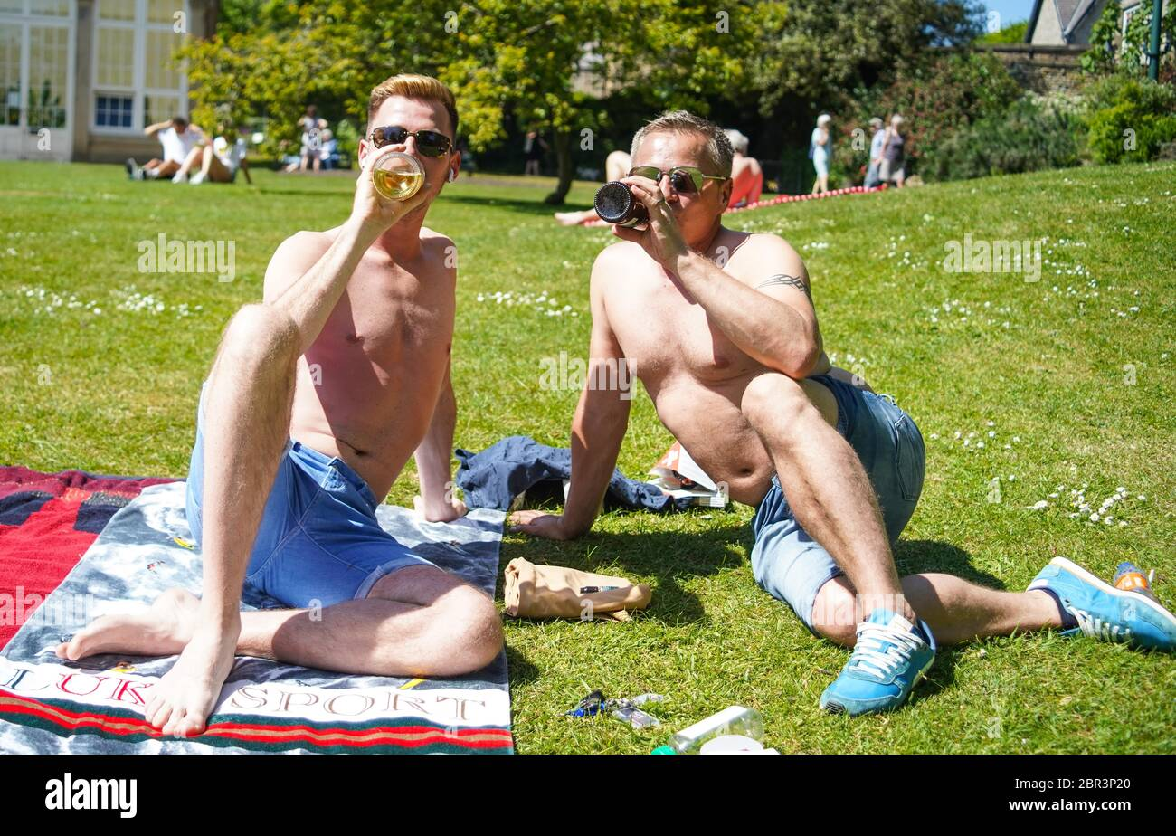 20th May, Sheffield, UK. Two friends drinking alcohol as they sunbathe in the Botanical Gardens, Sheffield on a warm day. The British government eased some measures allowing for the people to spend more time outdoors without restrictions Credit: Ioannis Alexopoulos/Alamy Live News Stock Photo