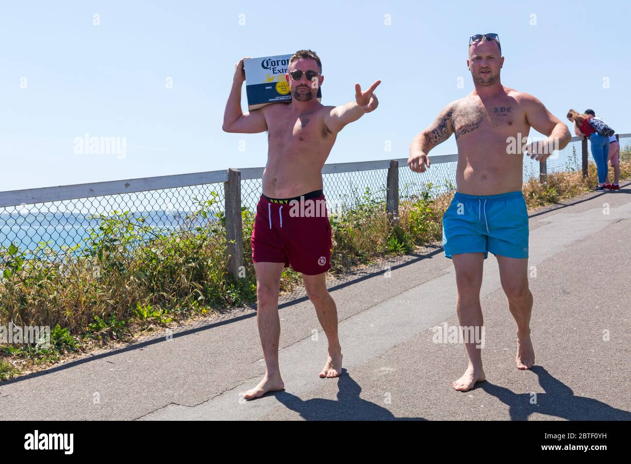 Bournemouth, Dorset UK. 25th May 2020. UK weather: scorching hot at Bournemouth beaches with clear blue skies and unbroken sunshine, as temperatures soar on Bank Holiday Monday. Sunseekers flock to the seaside and beaches are packed, with car parks full and cars left anywhere and everywhere. Ben and John head down to the beach with their supplies - a box of Corona! Credit: Carolyn Jenkins/Alamy Live News Stock Photo