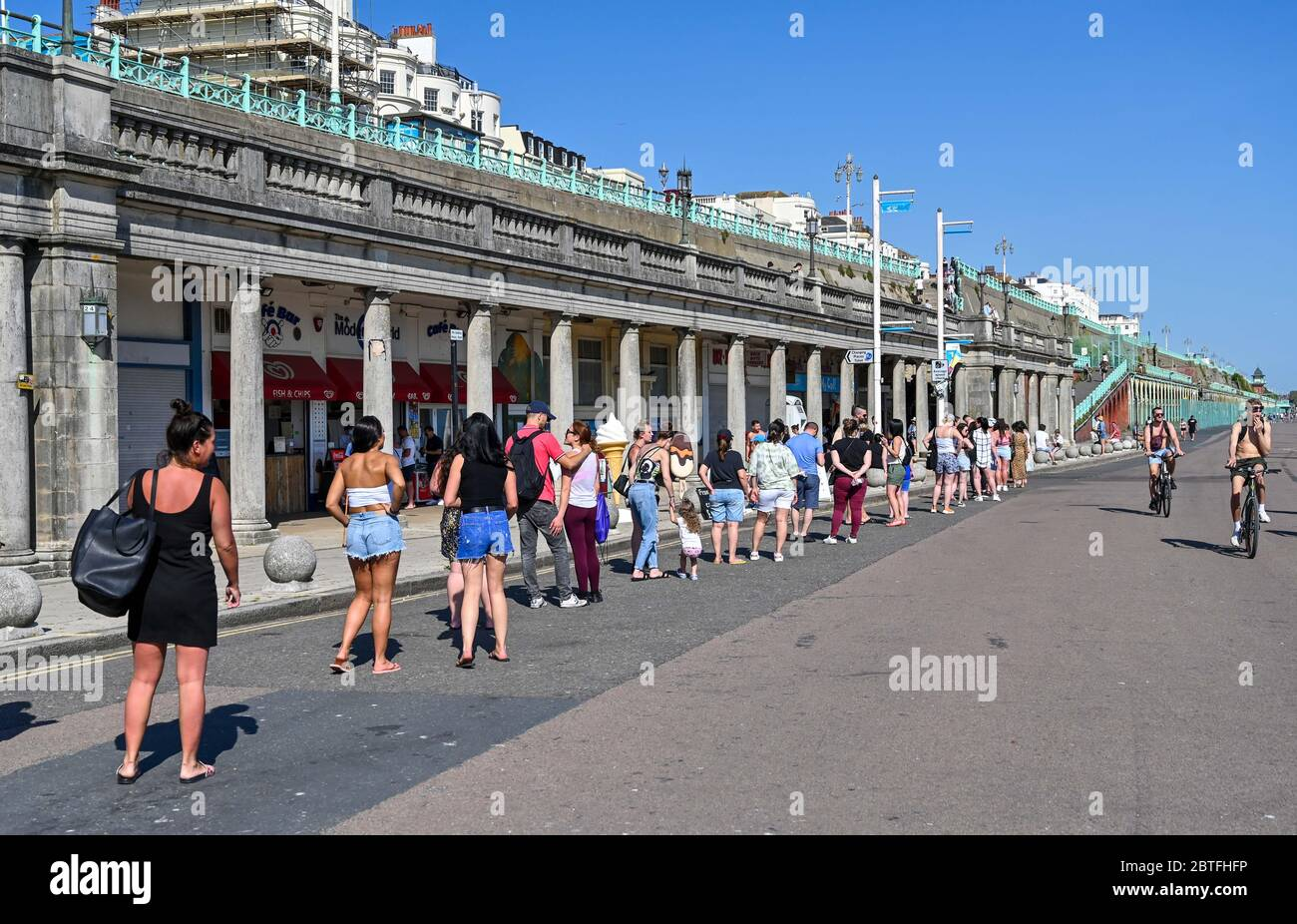 Brighton UK 25th May 2020 - Visitors queue for a public toilet in the late afternoon sunshine on Brighton beach and seafront as the bank holiday weekend draws to an end today on the south coast during the Coronavirus COVID-19 pandemic crisis  . Credit: Simon Dack / Alamy Live News Stock Photo