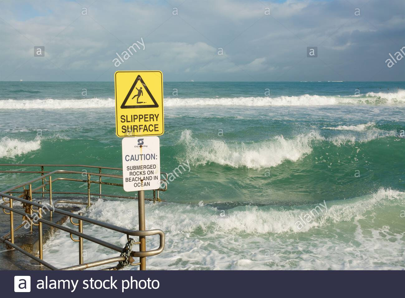 the-disability-access-ramp-at-mettams-pool-in-trigg-being-swamped-by-waves-from-a-high-swell-following-stormy-weather-perth-western-australia-2BTYM48.jpg