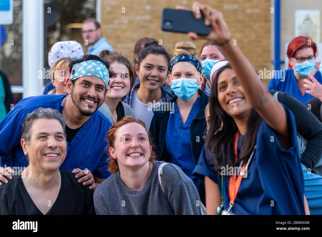 staff-at-final-clap-for-carers-at-8pm-thursday-outside-southend-university-hospital-essex-uk-ward-team-gathering-for-a-selfie-doctors-and-nurses-2BW0XXW.jpg