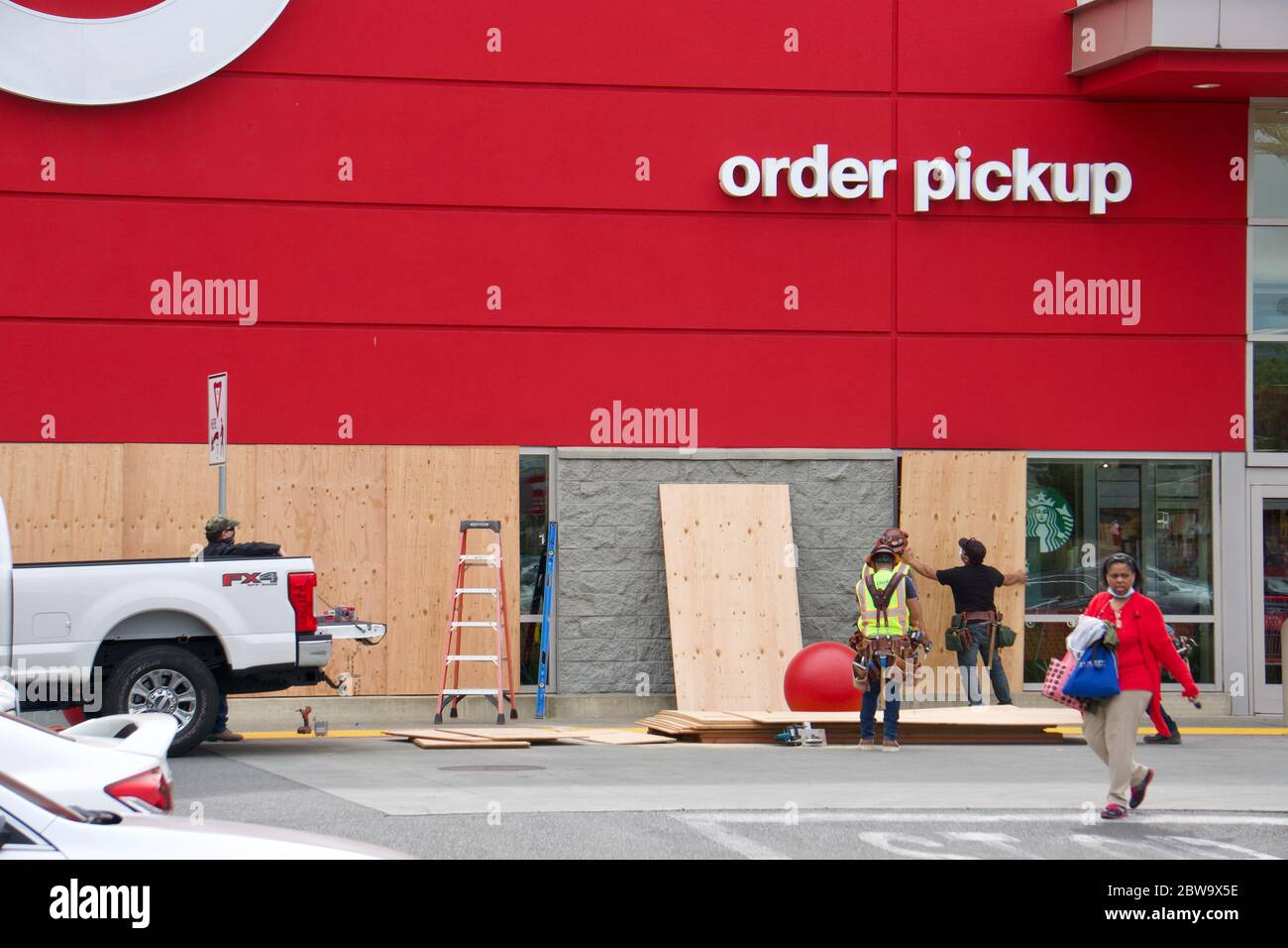 Workers board up Target store windows to safeguard against looters after the killing of George Floyd by a police officer in Minneapolis. Oakland, CA Stock Photo