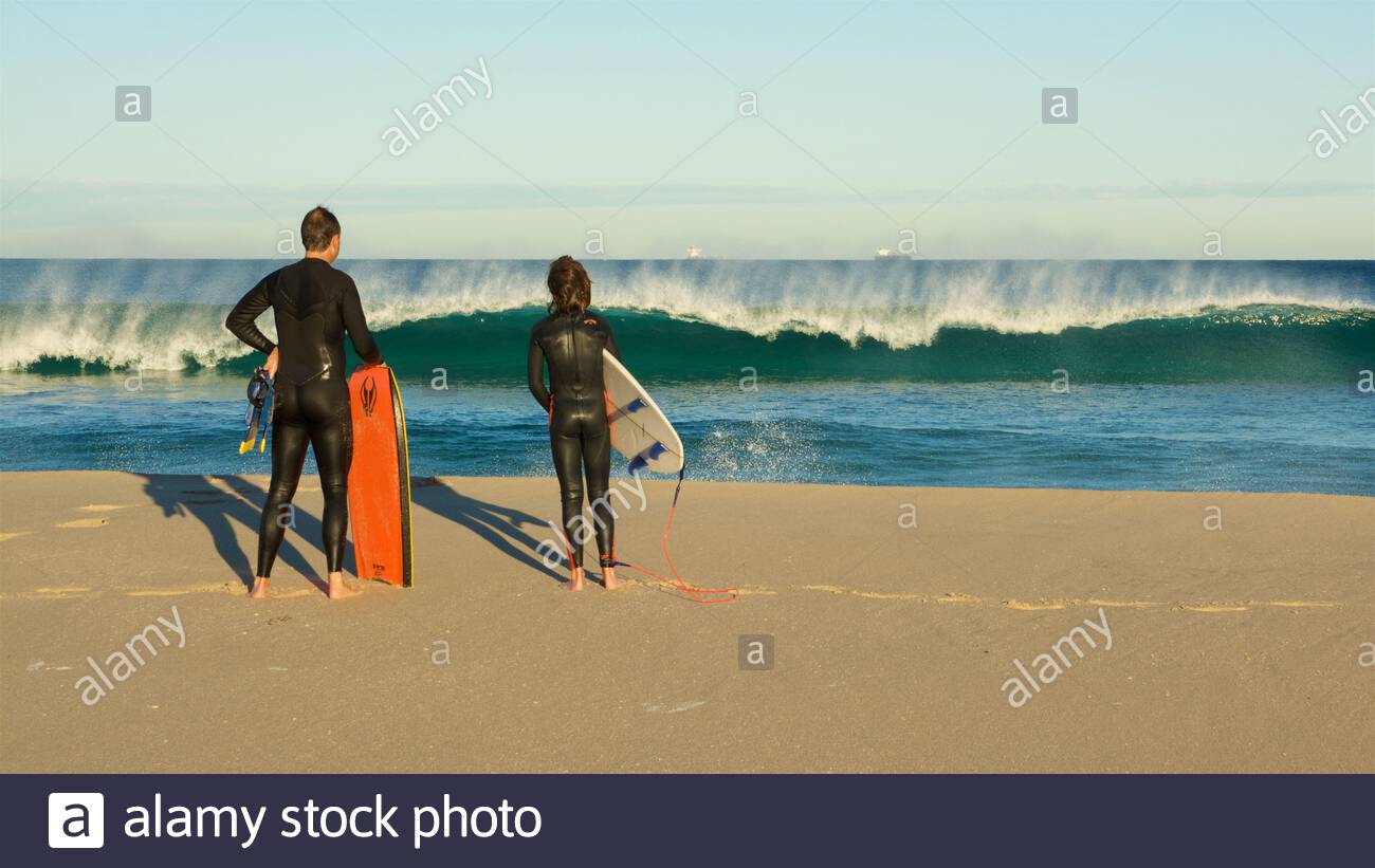 a-man-and-boy-with-their-boards-watching-a-wave-breaking-after-leaving-the-water-at-trigg-beach-in-perth-western-australia-2BX5XHM.jpg