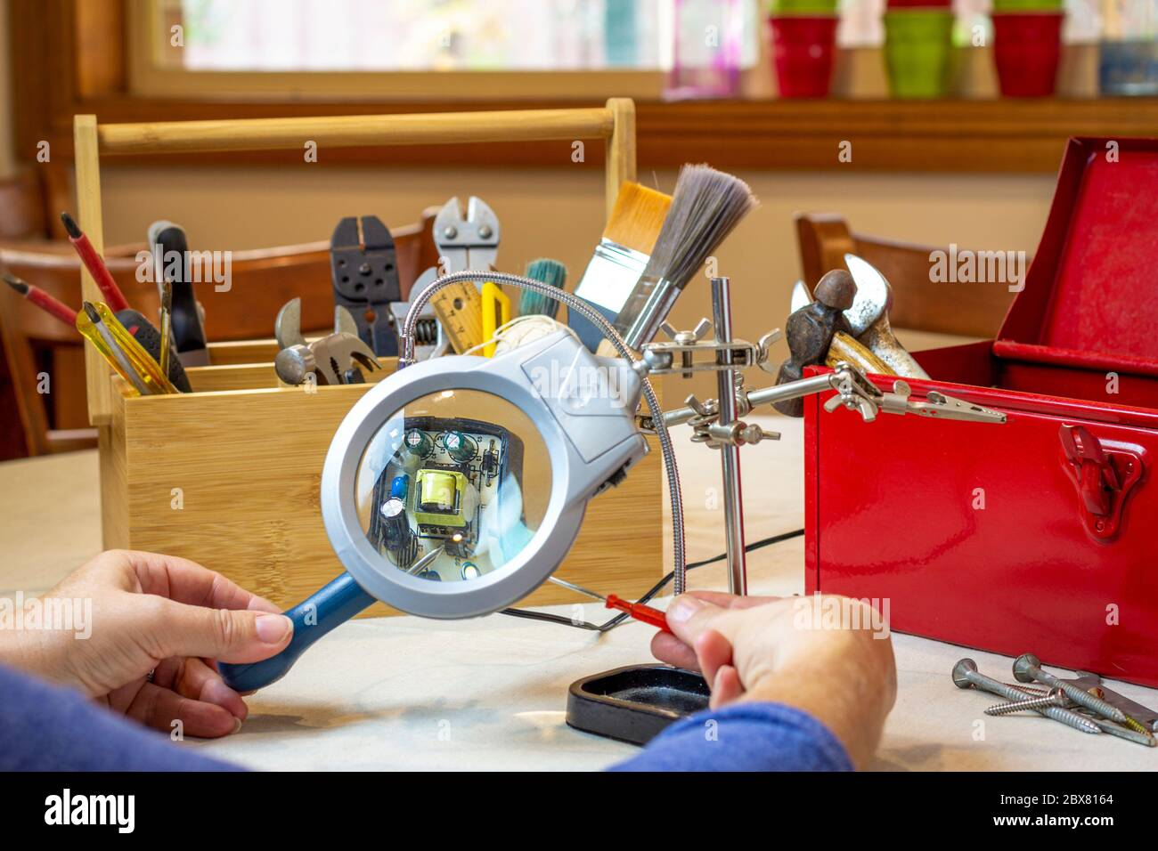Person using tools and magnifying glass repairing household item at community repair event at cafe, Repair Cafe movement, consumer activism to repair Stock Photo