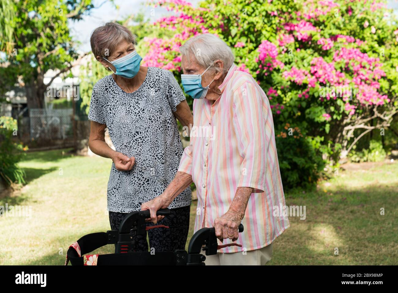 carer-helping-elderly-lady-to-get-exercise-in-garden-wearing-mask-2BX98MP.jpg