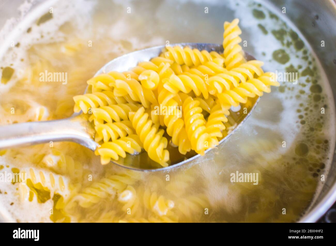pasta-being-cooked-in-a-pan-with-boiler-water-and-spatula-checking-for-pasta-2BXHHF2.jpg