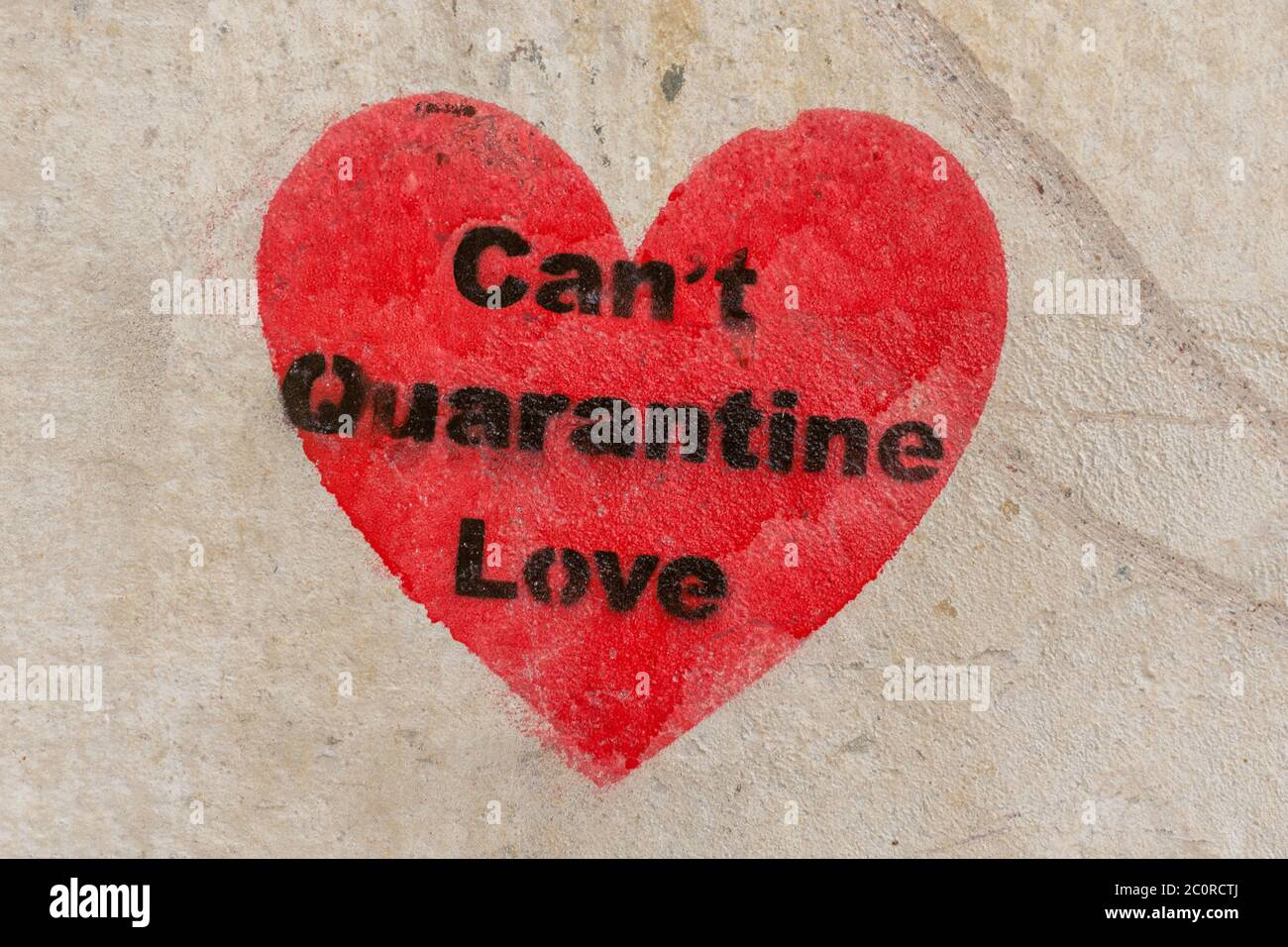 The words Can't quarantine love, in a red heart on a stone wall during the 2020 coronavirus covid-19 pandemic Stock Photo
