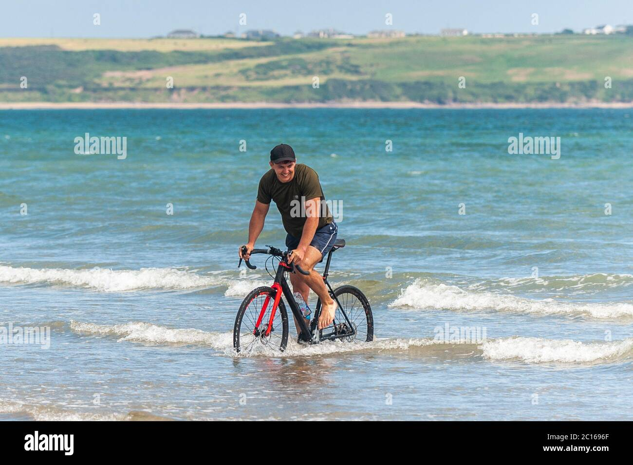 tramore-co-waterford-ireland-14th-june-2020-tramore-beach-was-busy-today-on-a-gloriously-sunny-day-with-highs-of-18-to-23-celsius-a-man-rides-his-bike-into-the-sea-to-cool-off-credit-ag-newsalamy-live-news-2C1696F.jpg