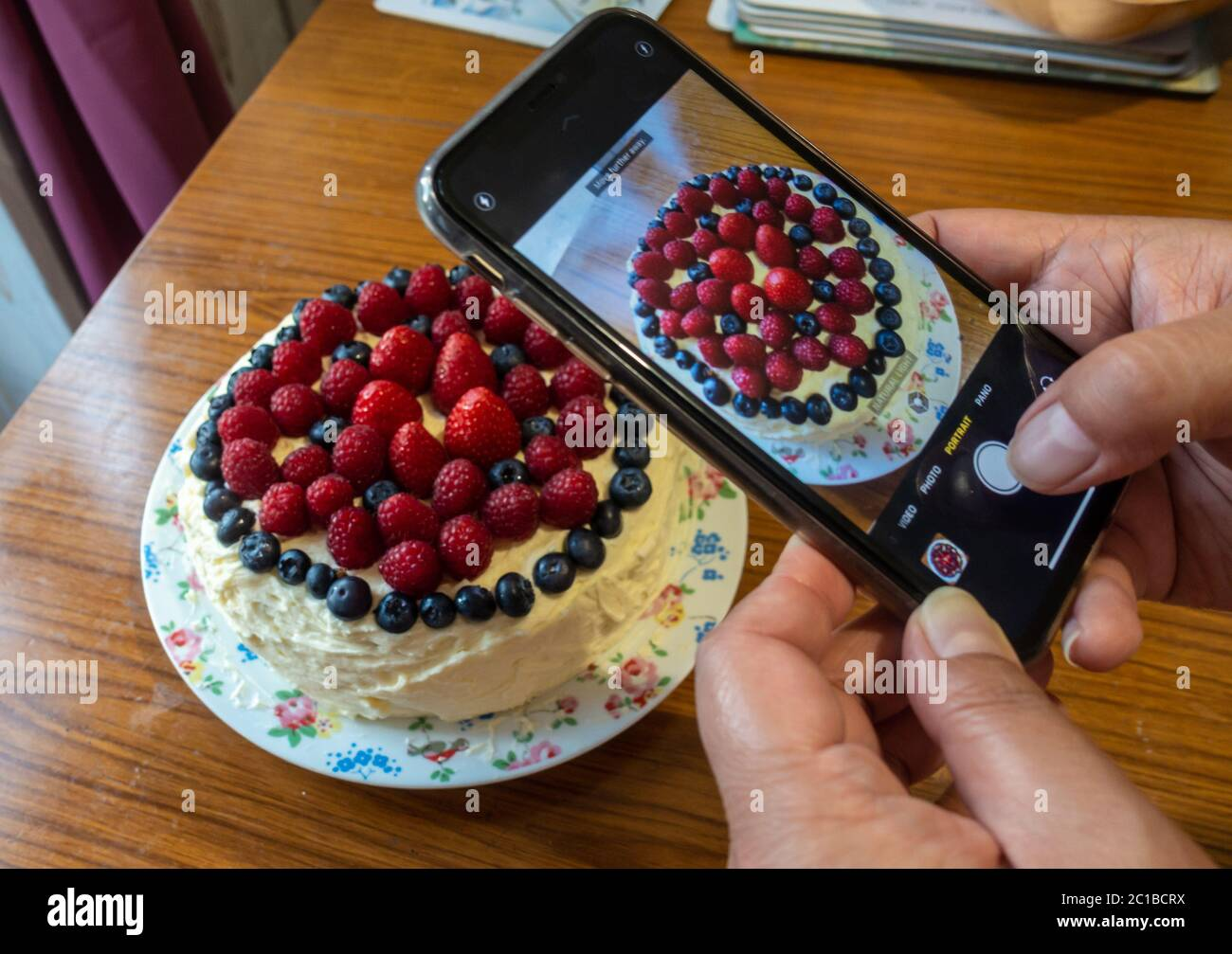 a-lady-uses-a-smartphone-to-take-a-photograph-of-a-freshly-made-cake-which-is-decorated-with-butter-icing-and-soft-red-and-purple-summer-fruits-2C1BCRX.jpg