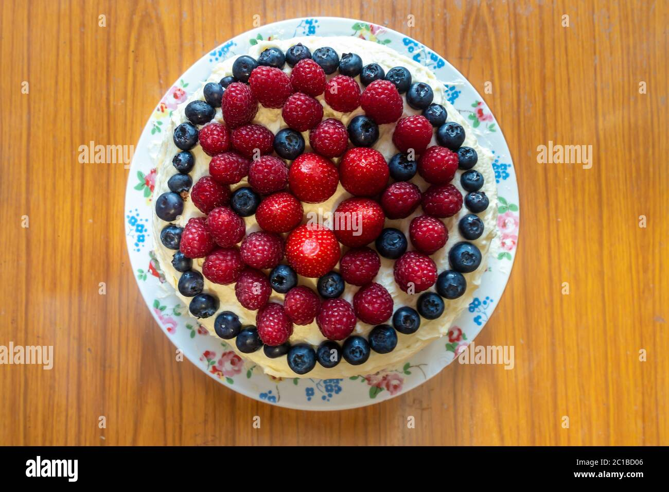 a-cake-decorated-with-butter-icing-and-summer-fruits-including-strawberries-raspberries-and-blueberries-2C1BD06.jpg