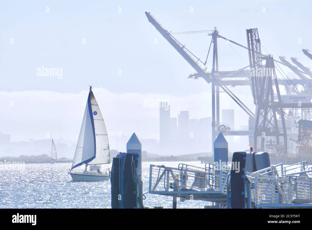 sailboat-entering-oakland-inner-harbor-at-jack-london-square-with-giant-shipping-cranes-and-docks-the-san-francisco-skyline-behind-oakland-ca-2C3Y5KT.jpg