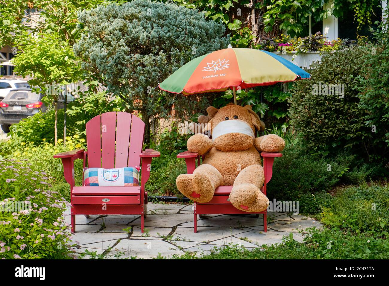 large-stuffed-moose-with-face-covering-sitting-a-lawn-chair-as-a-display-in-front-yard-of-ottawa-home-2C431TA.jpg