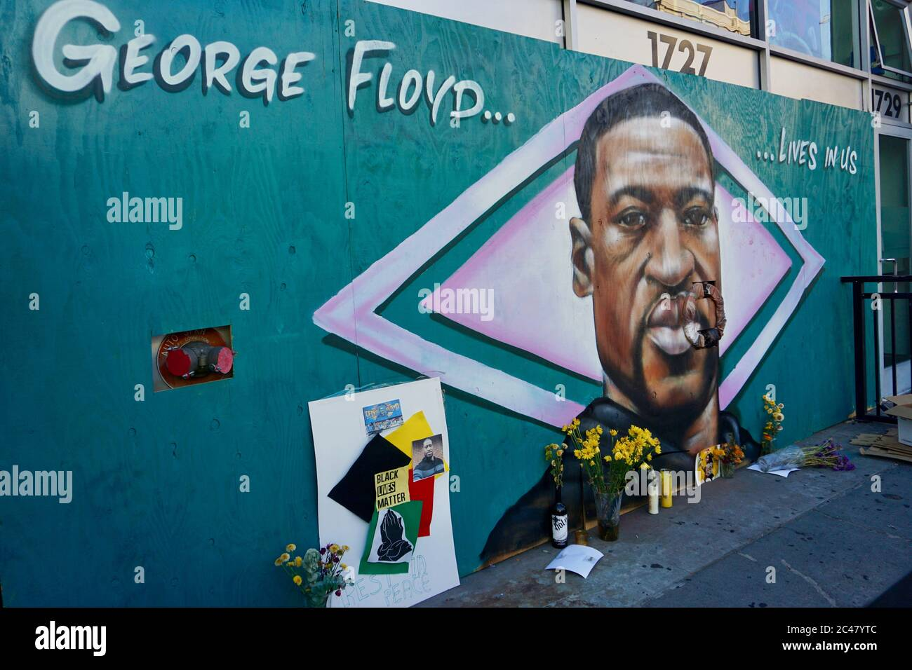 Black Lives Matter memorial and shrine to George Floyd. Mural by artist AmendTDK painted on boarded storefront. Downtown Oakland, California, USA. Stock Photo