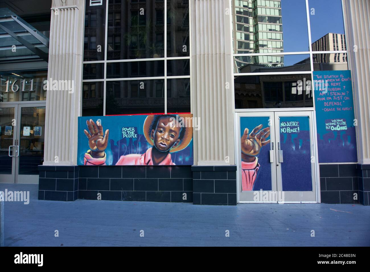 Black Lives Matter protest street art mural of a black boy with hands up on boarded building after George Floyd protests, Downtown Oakland. Stock Photo