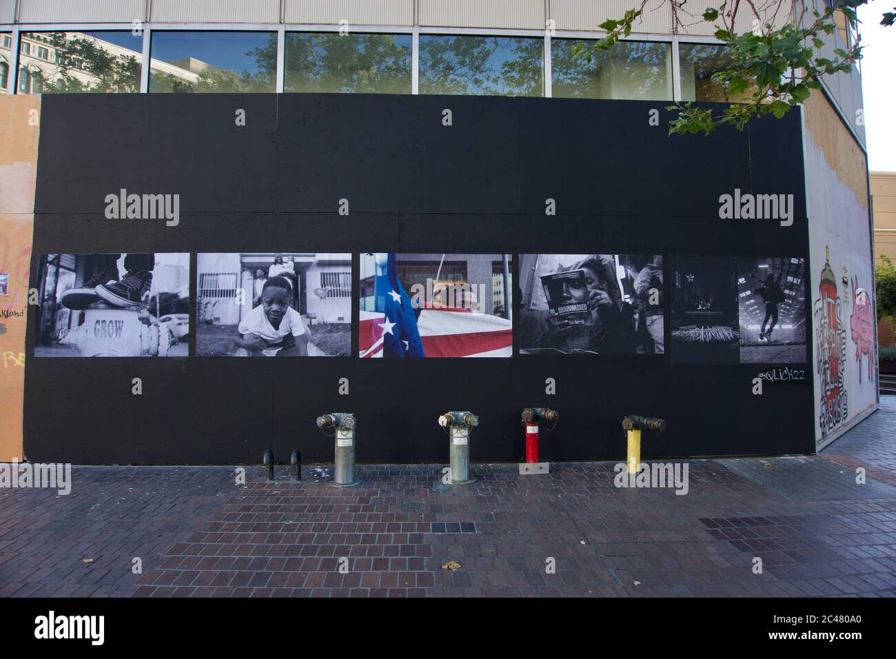 Black Lives Matter photographic street art with American flag on boarded up Walgreens after the killing of George Floyd and looting. Downtown Oakland. Stock Photo