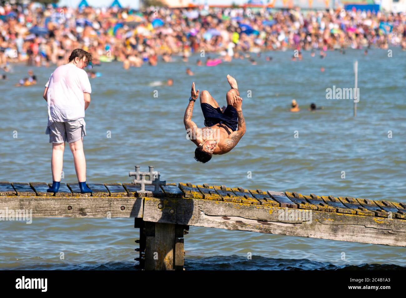 male-diving-into-sea-flipping-despite-the-covid-19-coronavirus-lockdown-crowds-of-people-have-travelled-to-the-beaches-of-southend-on-sea-essex-uk-2C4B1A3.jpg