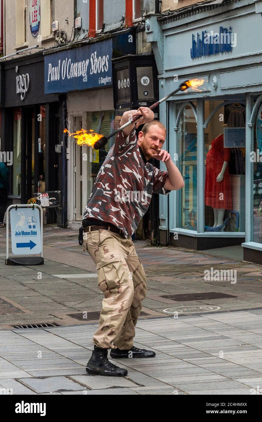 cork-ireland-27th-june-2020-a-man-entertains-shoppers-with-a-fire-stick-in-cork-city-gruby-grove-a-polish-artist-has-been-playing-with-fire-for-4-years-credit-ag-newsalamy-live-news-2C4HMXX.jpg