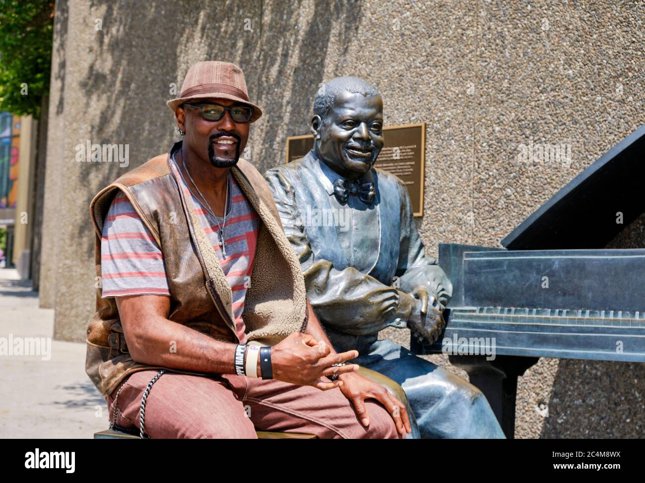 ottawa-canada-american-visitor-to-the-city-posing-sitting-next-to-the-oscar-peterson-statue-in-city-core-2C4M8WX.jpg