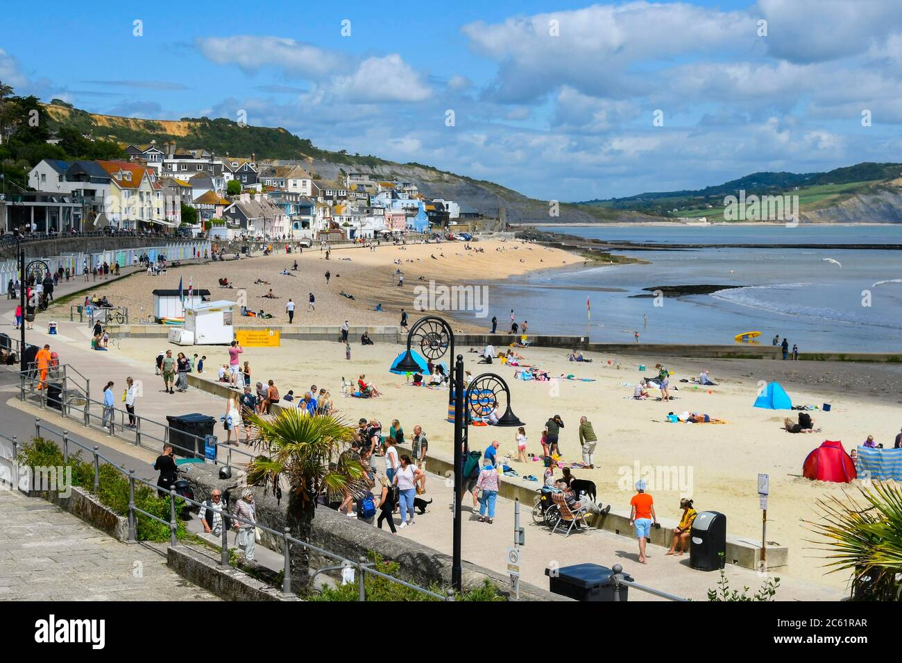 Lyme Regis, Dorset, UK.  6th July 2020.   UK Weather:  The beach is busy with families and sunbathers at the seaside resort of Lyme Regis in Dorset on a day of warm sunny spells.  Picture Credit: Graham Hunt/Alamy Live News Stock Photo