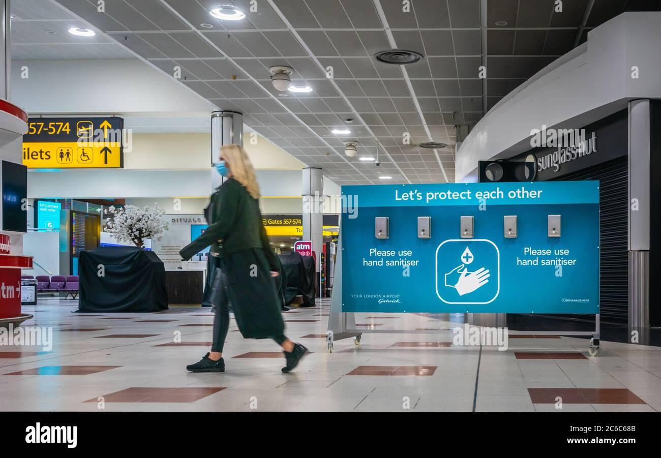 a-woman-wearing-a-face-mask-walks-past-a-hand-sanitiser-dispenser-station-at-gatwick-airport-during-the-global-coronavirus-pandemic-2020-england-uk-2C6C68B.jpg