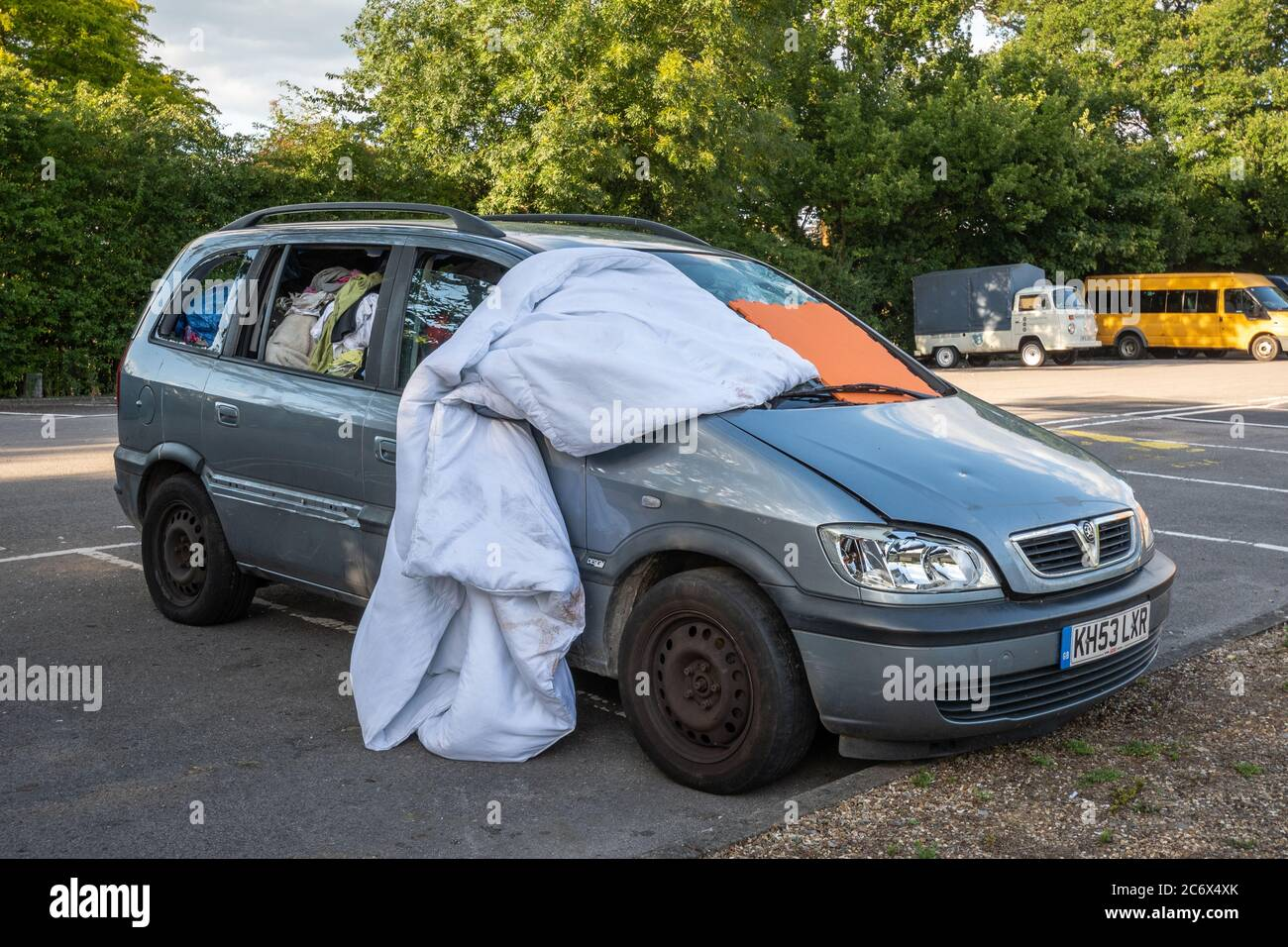 a-car-being-lived-in-by-a-homeless-person-full-of-clothes-and-belongings-with-the-front-windscreen-covered-uk-2C6X4XK.jpg