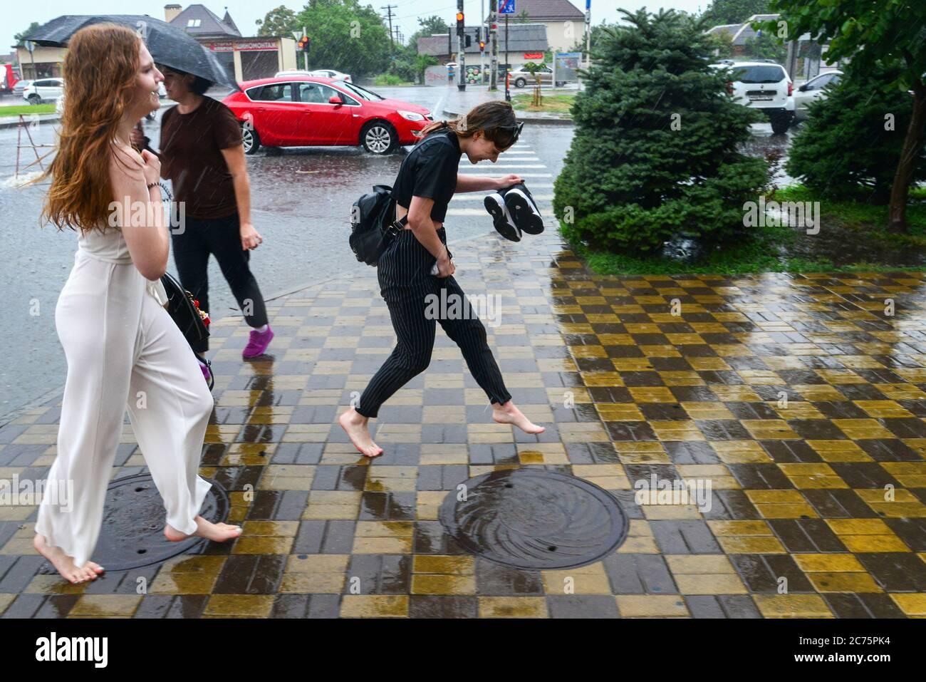 https://c7.alamy.com/comp/2C75PK4/krasnodar-russia-14th-july-2020-two-women-walk-barefoot-in-a-street-during-a-heavy-rain-credit-igor-onuchintassalamy-live-news-2C75PK4.jpg