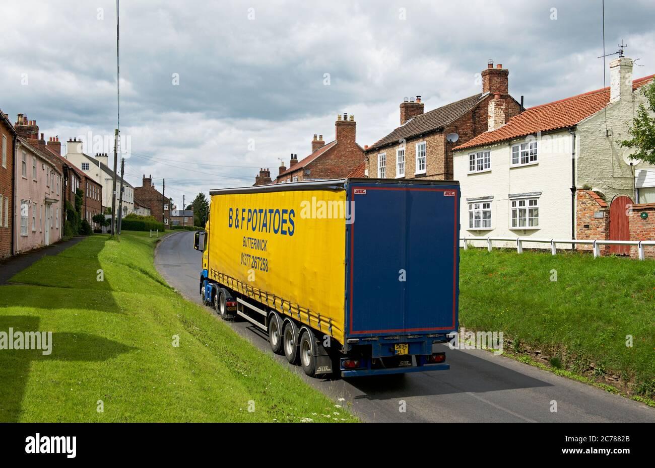 Lorry carrying potatoes through the village of Stillington, North Yorkshire, England UK Stock Photo