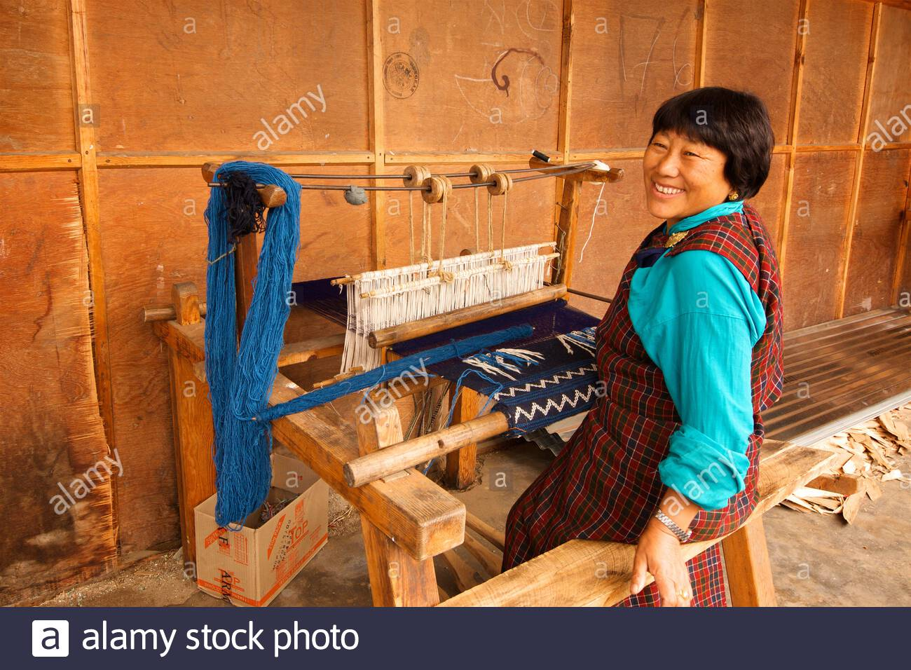 a-woman-demonstrating-the-use-of-a-traditional-wooden-bhutanese-loom-used-for-weaving-textiles-at-a-roadside-textile-store-bumthang-district-bhutan-2C78J04.jpg
