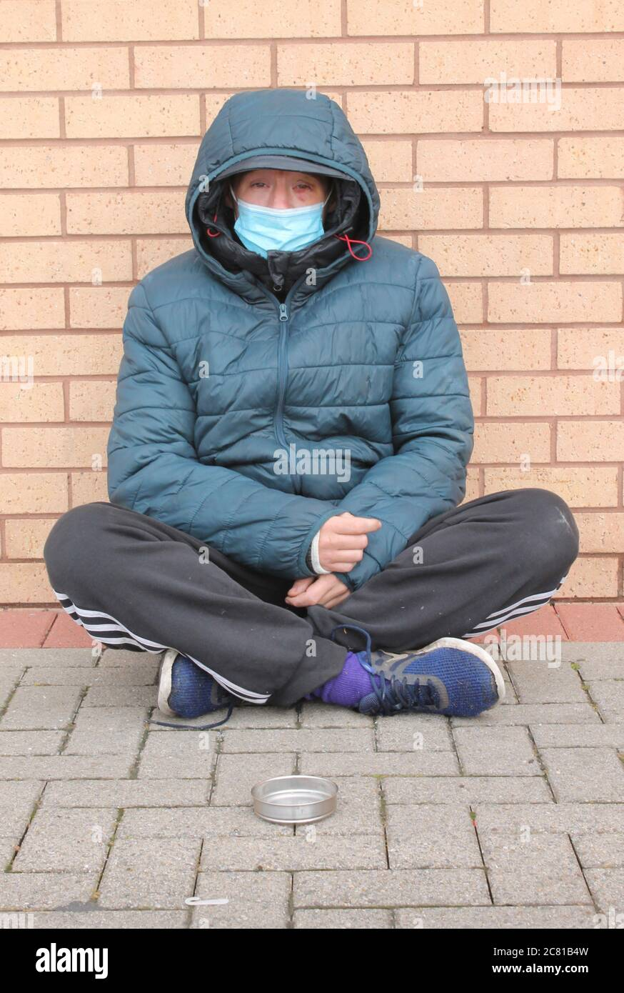 Homeless women with bruised eye, wearing a blue mask sitting on the floor with legs crossed begging for change Stock Photo