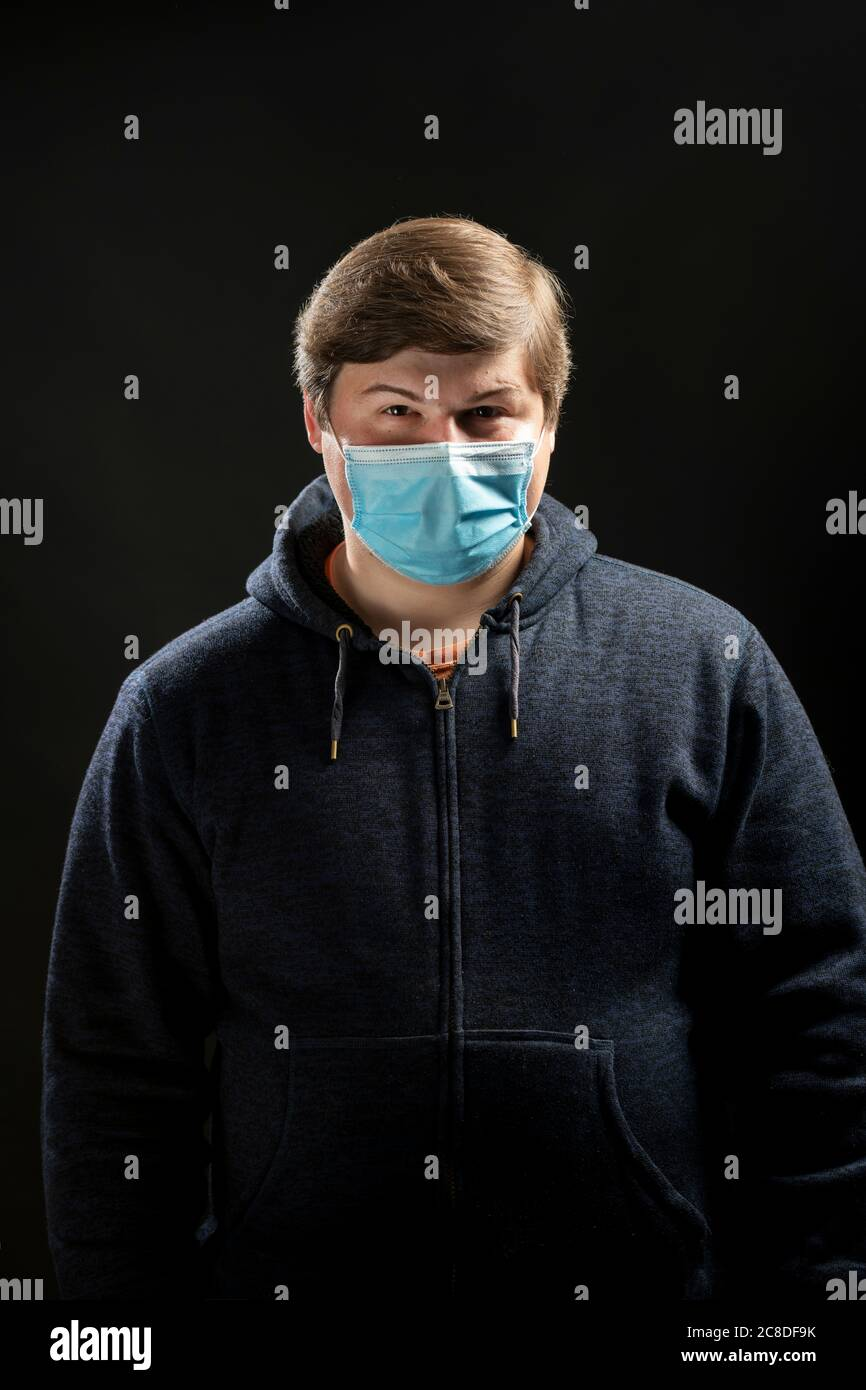 man-in-his-20s-twenties-with-a-medical-type-blue-mask-on-in-a-studio-mask-to-stop-the-spread-of-the-coronavirus-covid-19-2C8DF9K.jpg