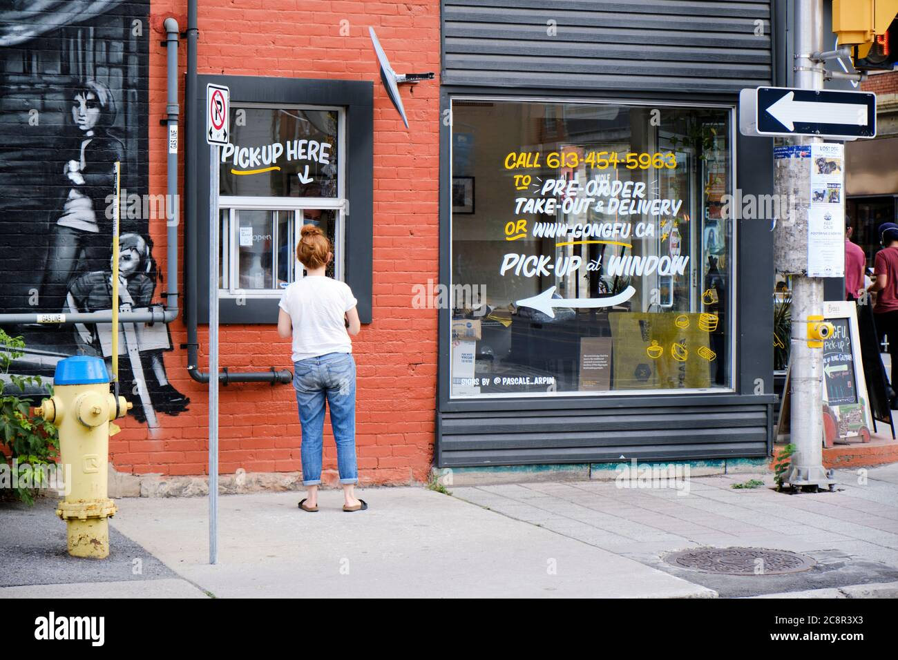 Young woman picking up food from window of Gong Fu restaurant in Ottawa during Pandemic 2020 Stock Photo