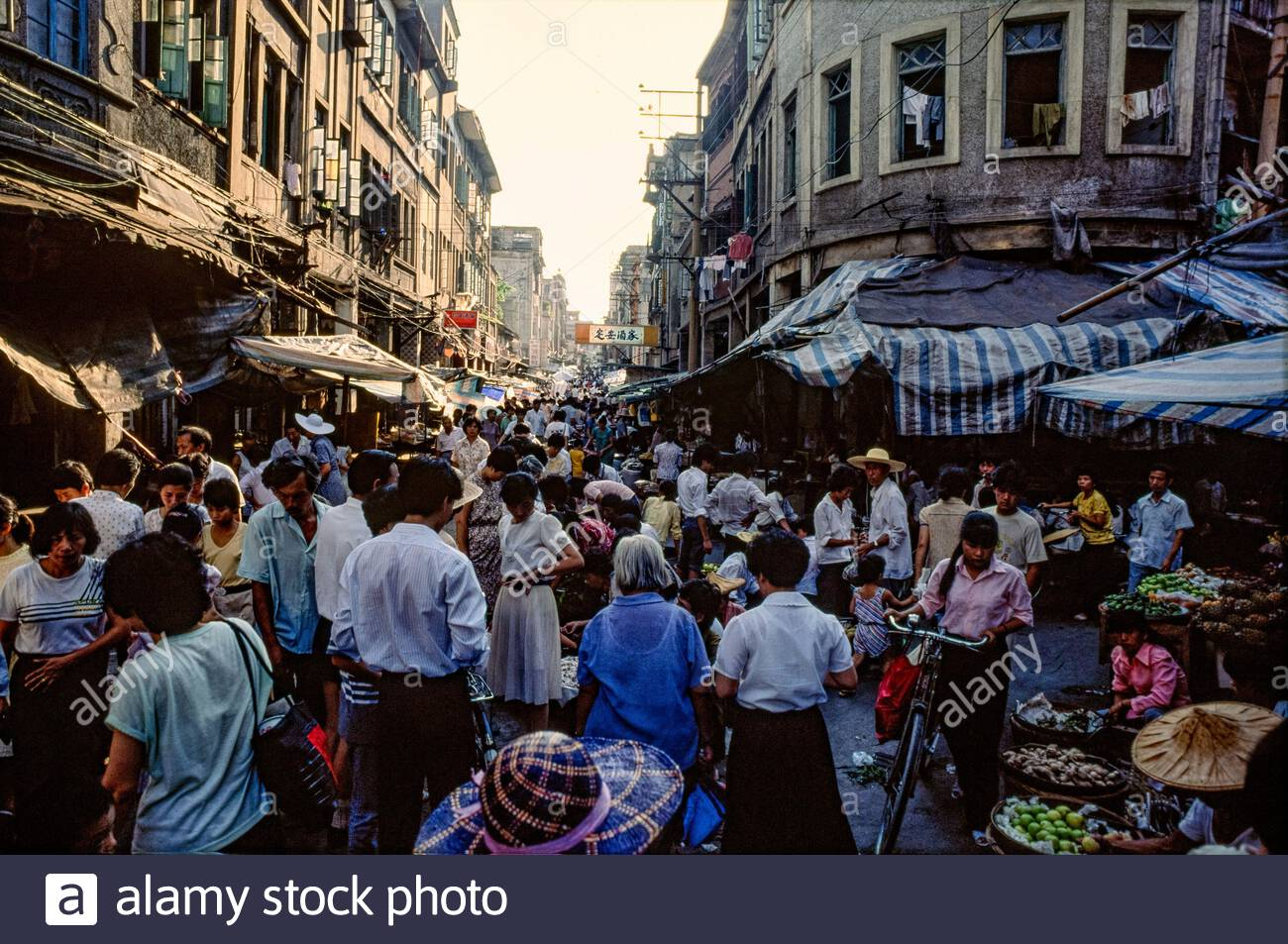 People buy and sell food and other items in a street market in Xiamen, 1990. Stock Photo
