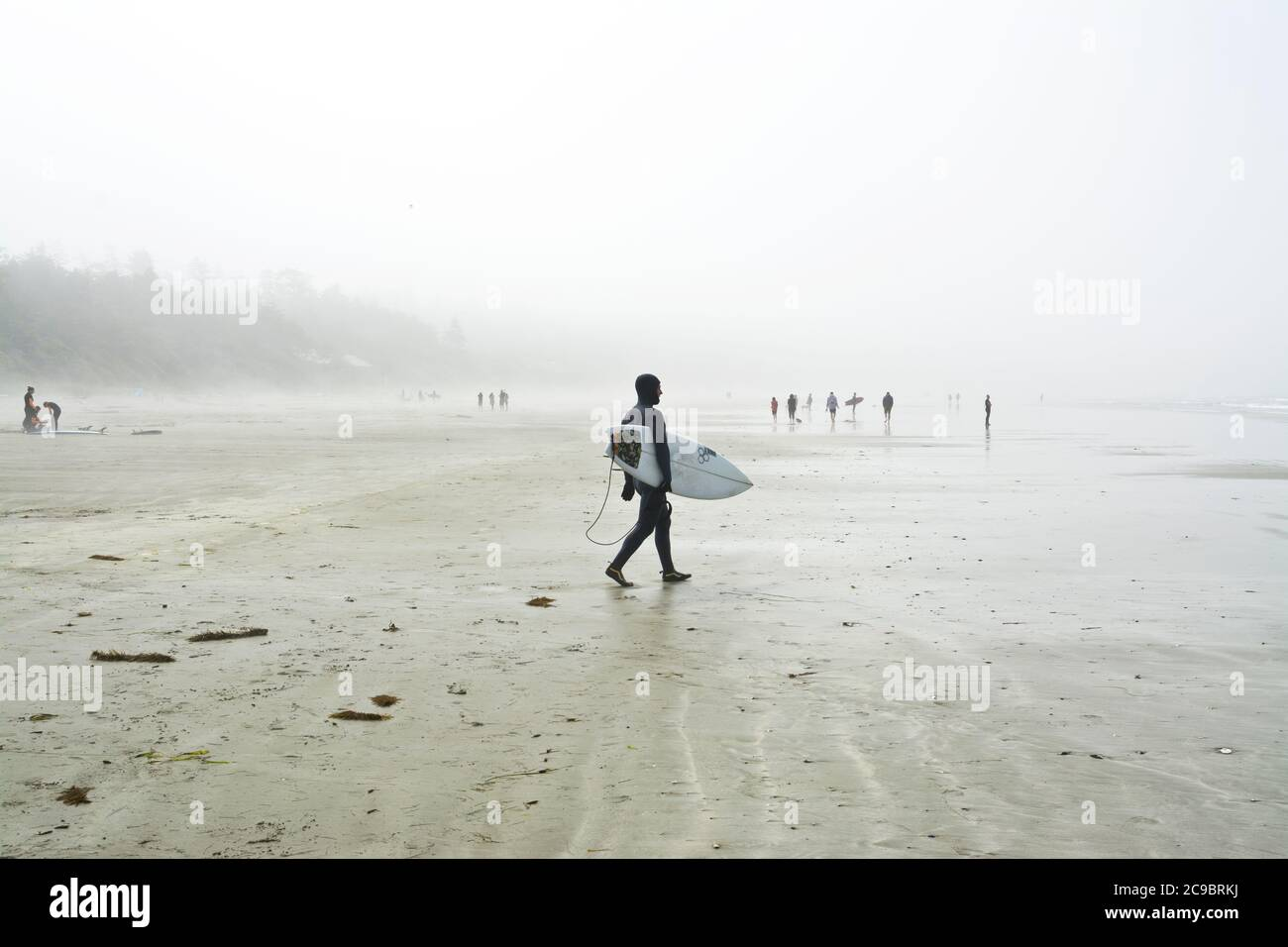 Surfer in wetsuit carrying a surfboard at Cox Bay Beach in Tofino, British Columbia, Canada.  Foggy day on the beach in Tofino, BC. Stock Photo