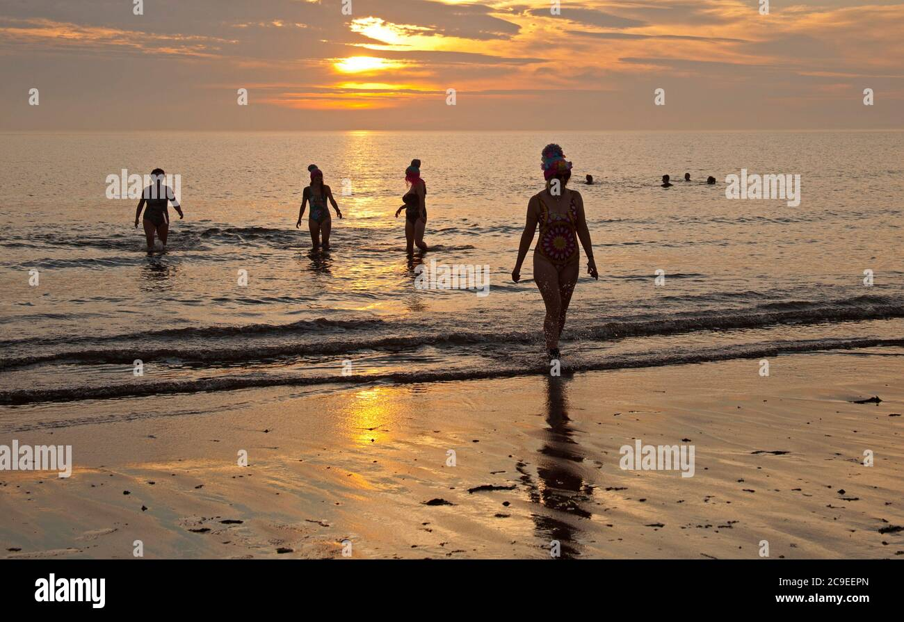 Portobello, Edinburgh, Scotland, UK. 31 July 2020. Sun was slow to appear from behind the clouds at dawn with temperature of 12 degrees. Forecast is for the mid to high twenties today. Pictured: Female Wild Swimmers enjoyed the sunrise activity. Credit: Arch White/ Alamy Live/News Stock Photo