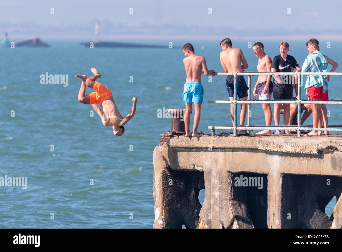 southend-on-sea-essex-uk-31st-jul-2020-with-the-forecast-high-temperatures-people-are-heading-to-the-seafront-to-cool-down-despite-the-covid-19-coronavirus-advice-in-the-thorpe-bay-area-to-the-east-of-southend-on-sea-people-are-out-enjoying-the-early-morning-high-tide-youngsters-are-jumping-into-the-sea-from-the-disused-barge-pier-off-gunners-park-2C9EX53.jpg