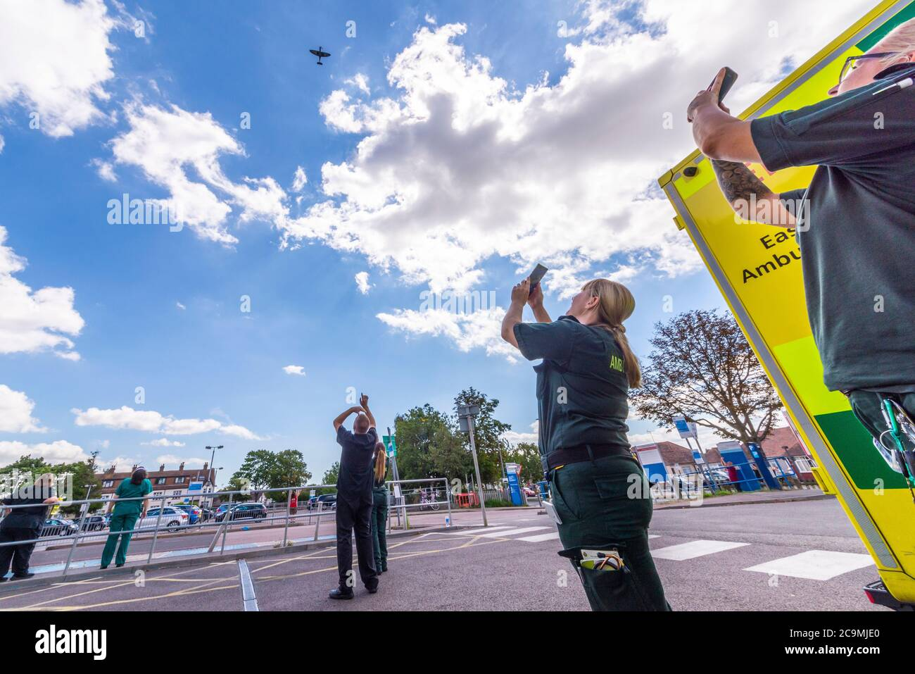southend-university-hospital-southend-on-sea-essex-uk-1st-aug-2020-the-aircraft-restoration-company-based-at-duxford-airfield-in-cambridgeshire-have-painted-thank-u-nhs-on-the-underside-of-their-blue-second-world-war-spitfire-in-honour-of-the-work-during-the-covid-19-coronavirus-pandemic-by-the-national-health-service-today-the-spitfire-has-flown-from-duxford-over-the-hospital-at-southend-before-heading-for-hospitals-in-kent-some-health-care-staff-came-out-to-watch-a-number-of-staff-at-southend-have-been-lost-to-the-virus-ambulance-crews-photographing-and-videoing-with-phones-2C9MJE0.jpg