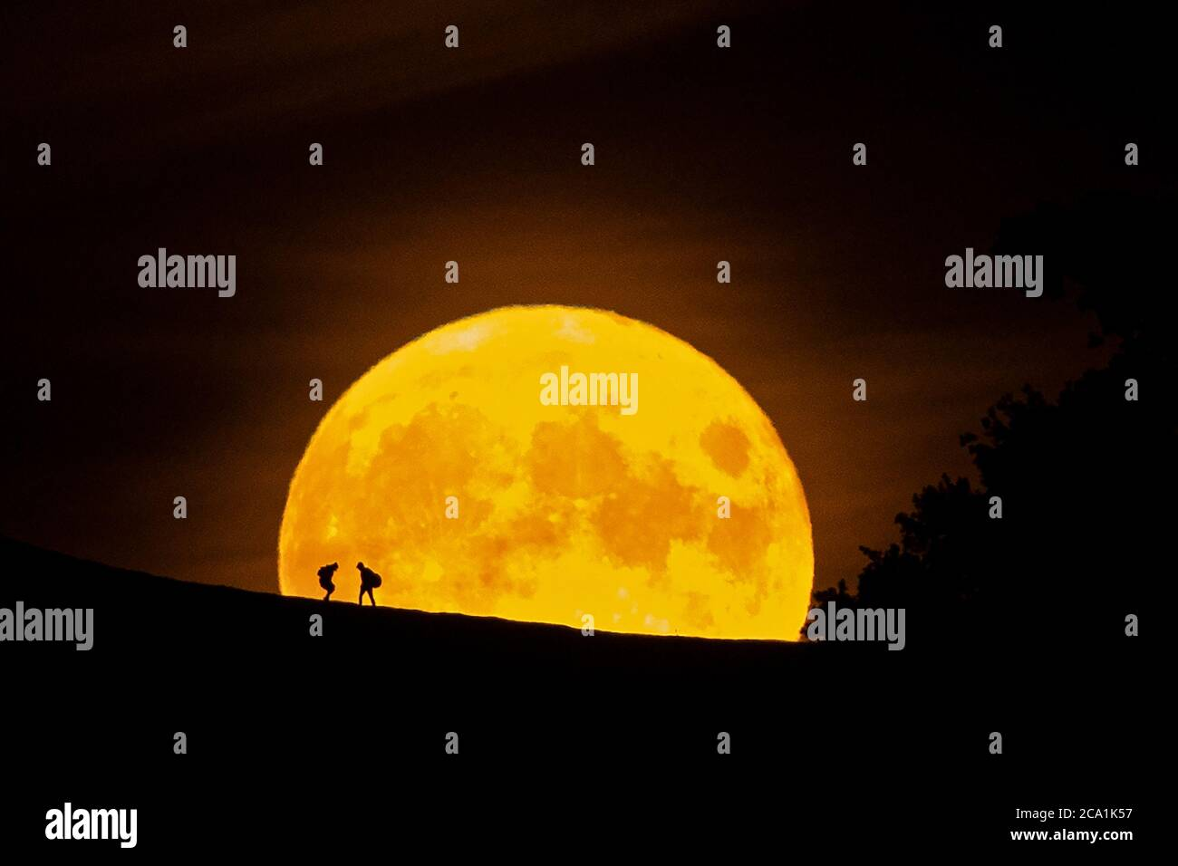GLASTONBURY, UK. 03rd Aug, 2020. Hikers stop to admire the view of the full moon as it rises over Somerset (Photo by Mitchell Gunn/Espa-Images) Credit: European Sports Photo Agency/Alamy Live News Stock Photo