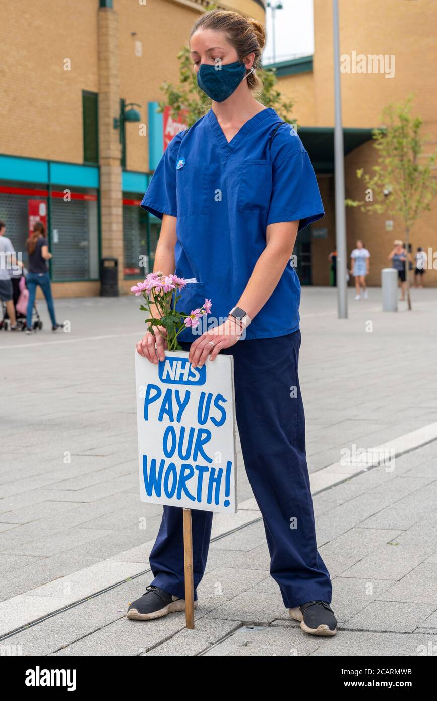 a-female-nurse-in-scrubs-pausing-to-honour-the-health-staff-killed-by-covid-19-at-basildon-essex-uk-pay-protest-head-bowed-in-remembrance-2CARMWB.jpg