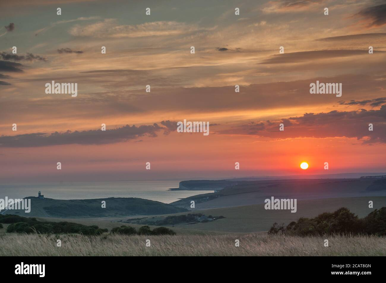 Eastbourne, East Sussex, UK. 8th Aug, 2020. Amazing colours & interesting clouds at sunset. A glorious end to a scorching day on the South coast. The Belle Tout lighthouse left of centre, overlooking Birling Gap toward Seaford & Newhaven. Taken from Beachy Head area. Credit: David Burr/Alamy Live News Stock Photo