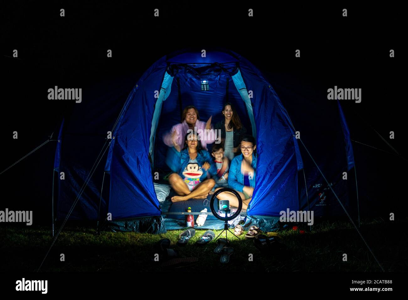friends-sit-together-in-a-tent-in-the-dark-and-make-a-tik-tok-video-using-a-ring-light-to-hold-a-phone-and-provide-light-2CATB88.jpg